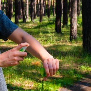 lány az erdőben sprayvel védekezik a rovarok ellen