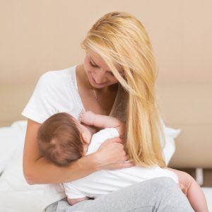 fiatal anyuka szoptatás közben gyermekével